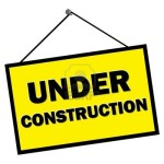 9579863-under-construction-sign-hanging-from-nail-isolated-over-white